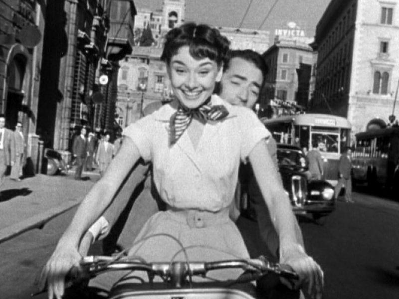 """Audrey Hepburn conduce una Vespa por las calles de Roma con Gregory Peck atrás (""""Vacaciones en Roma"""")."""