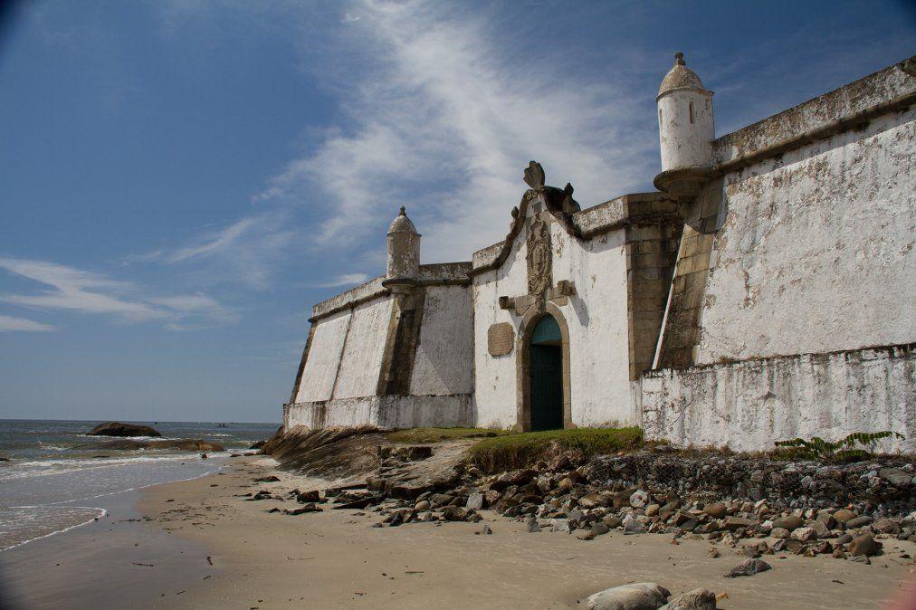 La Fortaleza de Nossa Senhora dos Prazeres se ubica con sus cañones y siluetas de cuento en una punta de la playa.