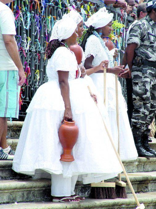 Las bahianas caminan en procesión cargando cántaros con agua perfumada y flores blancas.