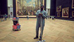 """Assane, disfrazado de personal de limpieza en el Museo del Louvre (París), a espaldas de Las bodas de Caná. Así, podemos inferir que mira de frente y sin pestañear a la verdadera reina del Louvre: """"La Gioconda""""."""